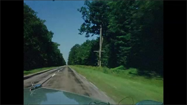 1950s: UNITED STATES & CANADA: view along road from car. Boats leave lock gates. Road trip in rural area. Trees by road.