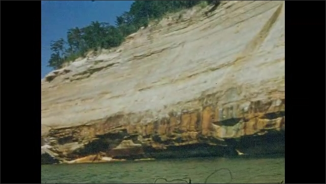 1950s: UNITED STATES & CANADA: view of sea cliff from boat. Colorful rock layers in sea cliff. Trees of cliff top. Mechanical weathering of rocks.