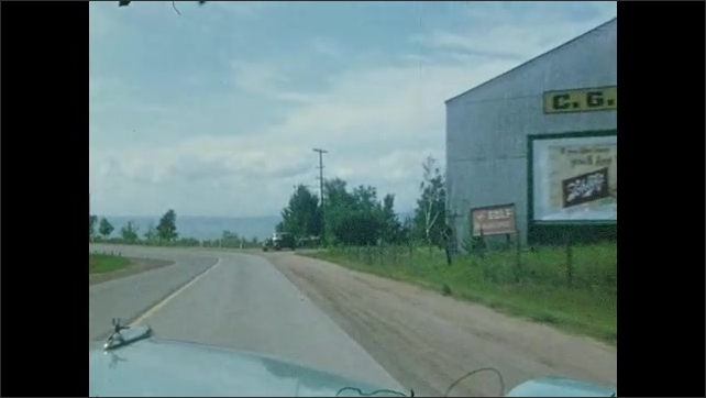 1950s: UNITED STATES & CANADA: view along forest road from car window. Straight road through forest. Car by road. Road trip by sea.