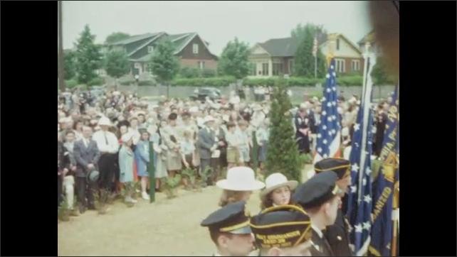 1940s: Crowd gathers at war memorial to listen to speech.