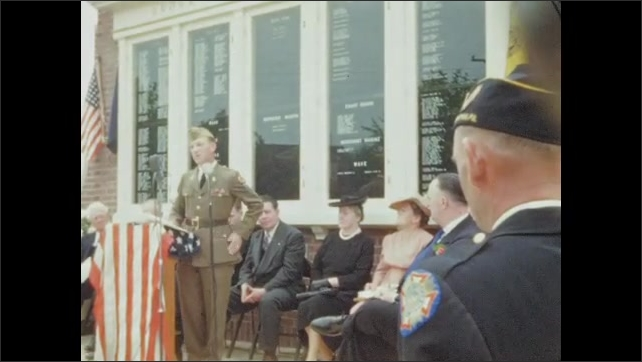 1940s: Soldier speaks to assembled crowd at war memorial. People applaud as man leaves podium. Soldier rises to speak at microphone.