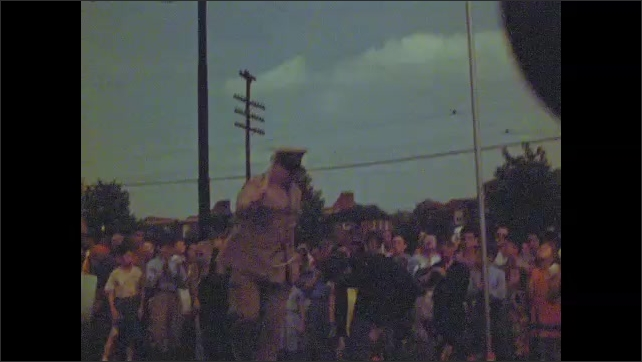 1940s: Man in uniform pulls line on flagpole. American flag rises up flagpole. Soldiers tie off line on flagpole. Crowd walks through lawn. Man speaks at announcer box.