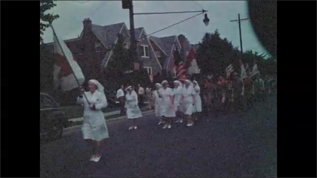 1940s: Marching band in parade. Red Cross nurses march in street parade. Boy and Girl Scouts carry flags and march in parade.