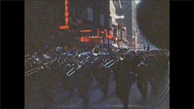 1940s: People march through neighborhood parade. Uniformed marching band walks through city streets parade. Women in uniform carry flags in parade. Soldiers in jeeps wave at crowds in parade.