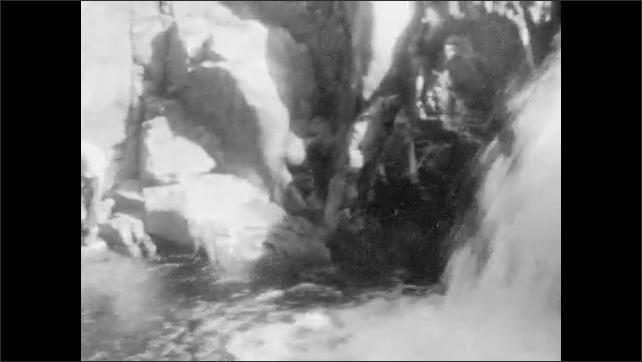 1920s: Bridge over stream. Two women stand on riverside. Man and child splash in river near waterfall. Man and girl pose on rocks near waterfall.
