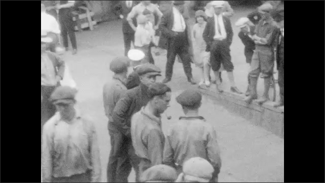 1920s: Boat pulling through docks then passed downtown. Men standing around docks. Boxes stacked at docks. Sailors tying knots with rope.