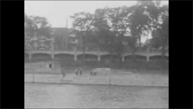 1920s: Two people with bikes on city street. People standing around docks. Boat pulling out of harbor. Boat goes passed homes along shore. Boat goes passed docked boats in harbor.