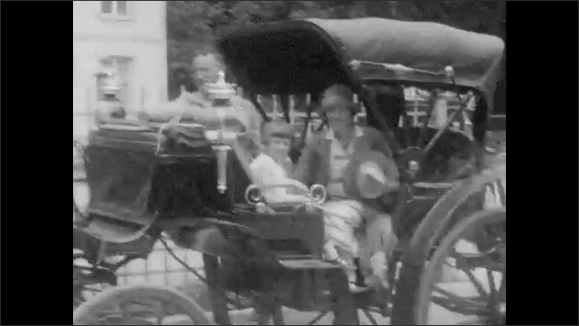 1920s: Church steeple. People walking up steps on knees. Large building. Woman, man and girl in carriage attached to horse. Two kids sit in carts attached to dogs. People sitting in back of truck.