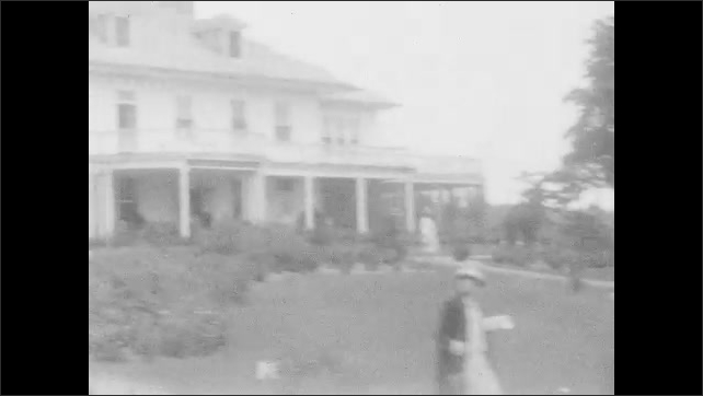 1920s: Traveling down road, passed houses in the countryside. Group of people going into building. Waterfall. Tram tracks lead down into building. Girl.