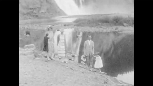 1920s: Two women in tram car. Waterfall. Family walks along path at base of waterfall. Tram rides down tracks.