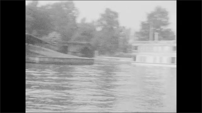 1920s: Boat named Kingston drives through water. Side of boat named Kingston. Stone archway over water. House surrounded by water. House along shore. Other boats in water. Building on shore.