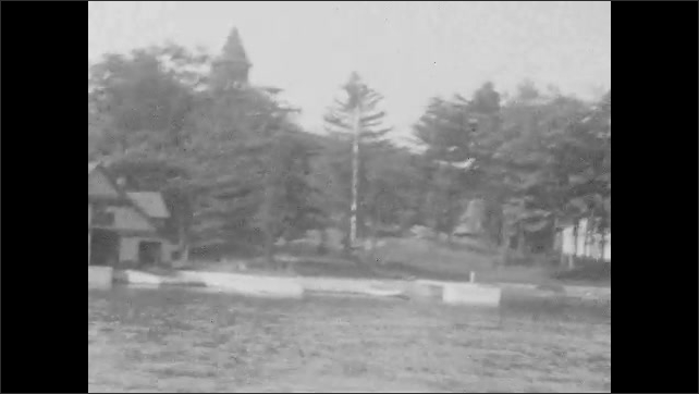 1920s: Tall building on shore as boat goes by. More houses along shore while going by on boat. Island in water.