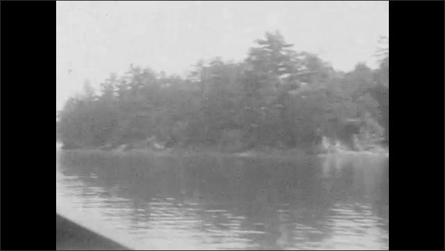 1920s: Traveling on boat passed small islands in water. Houses on islands while passing by on boat.