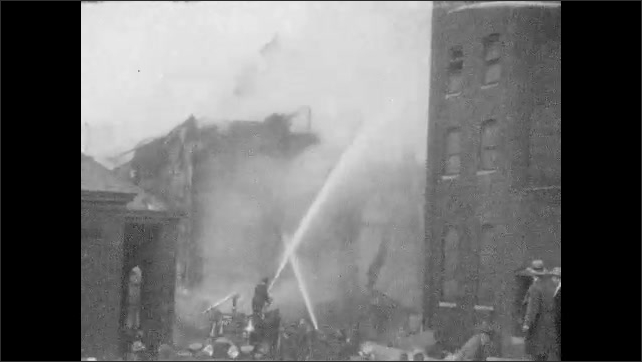 1920s: Firefighters battle fire in large building.