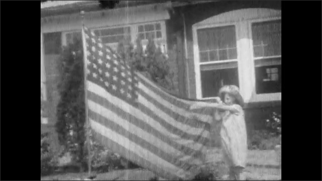 1930s: flower grows on trellis. girl in hat sniffs rose. child holds end of United States of America flag with 48 stars in front yard. female jumps rope near water sprinkler, road and houses.