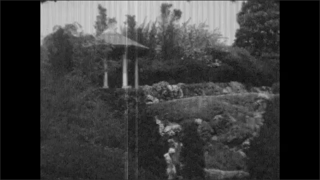 1930s: large mansion with windows and outdoor staircases sprawls over a cliff near edge of water with waterfalls, bushes, trees, flowers, plants and landscaping.