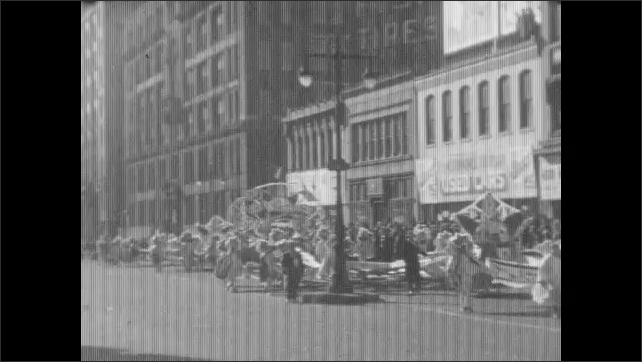 1930s: car drives down road near buildings. men and women stand near police officer on side of highway as autos drive past and enter rotary. people in costumes parade down street carrying float.