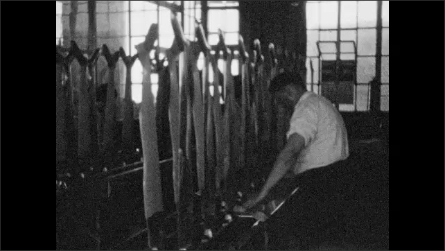 1920s: Male worker pulls off and puts stockings on forms at a textile mill.