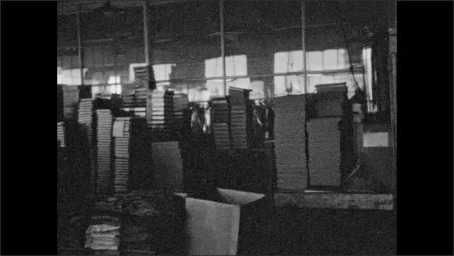 1920s: Women workers sit and stand at tables, folding and boxing stockings. Stacks of boxes. Women fold manufactured clothing in mill.