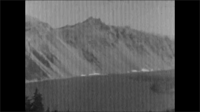 1920s: OREGON, UNITED STATES: view across lake. Trail to Lake sign. Lady and girl walk by building.
