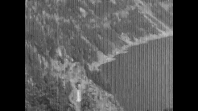 1920s: Man in suit and tie walks hand in hand with little girl on Crater Lake trail. Woman and little girl stand together, Man in suit looks over rim of Crater Lake. View from boat on Crater Lake.