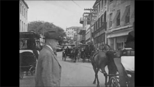 """1930s: Text reads """"A VISIT TO BERMUDA.""""  Seaside town.  City street.  Text reads """"Bermuda is graced with many modern and beautifully located hotels.""""  People walk around resort."""