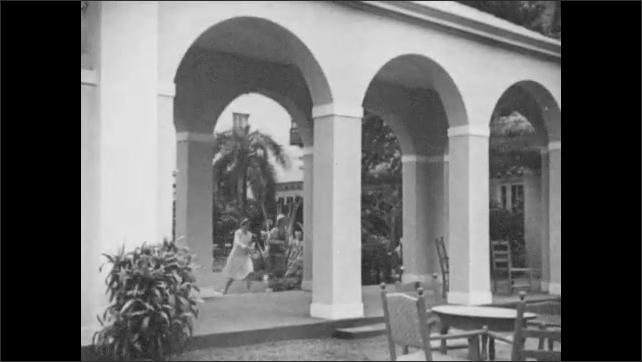 1930s: Hotel.  People walk through grounds.  Women watch boats from bridge.