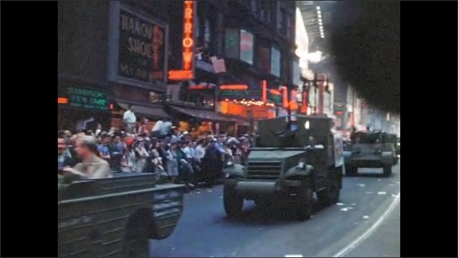 1940s: UNITED STATES: army vehicles in street parade. Tank drives through street. Armed forces march in parade.