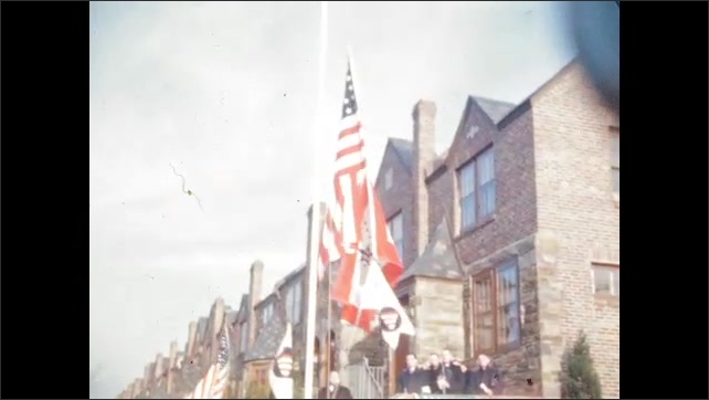 1940s: UNITED STATES: men stand around flag. Men raise flag s. Flags blow in wind