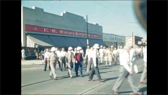 1940s: UNITED STATES: Lady leaves small building. Woolworths exterior. Men in costumes in parade.