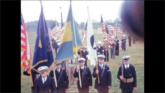 1940s: UNITED STATES: people stand in shape on ground. Uniformed men in field. People hold flags.