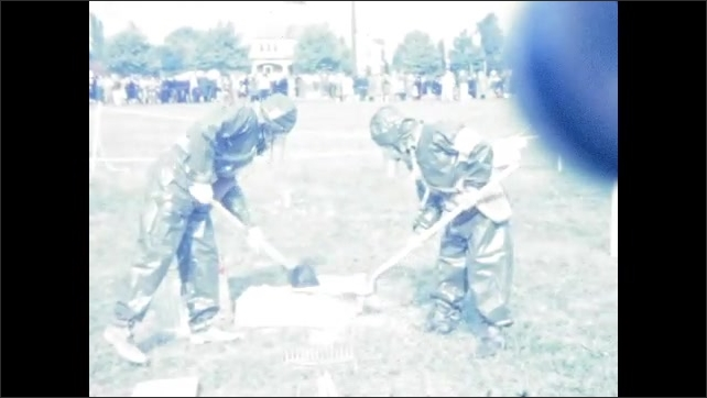 1940s: UNITED STATES: man wears gas mask. Man lights explosives. Men set up explosion in field.