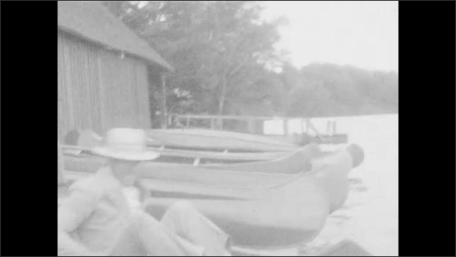 1920s: Man, woman, and children sit in canoe, man fishes. Man, women, and children walk on dock.