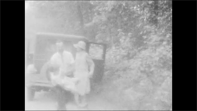 1920s: Man spins around and dances. Family looks at plants. Car parked on roadside. Man picks up women and children playfully.
