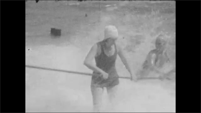 1920s: Adults and children play in the ocean, hold onto rope, play in the waves.