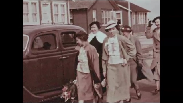 1930s:  Women and girls carry dog and exit screened in porch. Women and men in formal wear walk around parked cars and wave. Man chases dog on street.