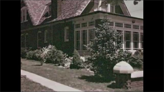 1930s: Large brick home with sun room. Bushes and flowers sway in wind outside of large brick home.