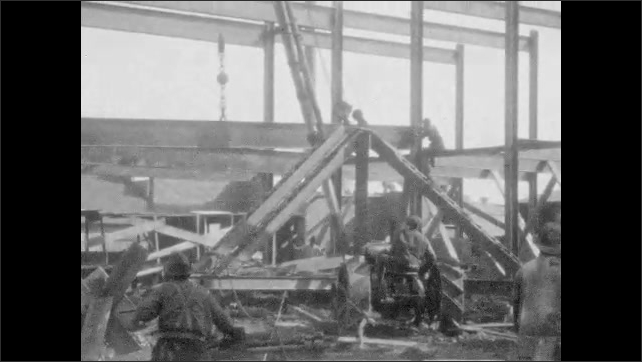 1920s: UNITED STATES: men on construction site. Men build brick wall. Man looks at camera. Steel girders on construction site. Crane lifts girder