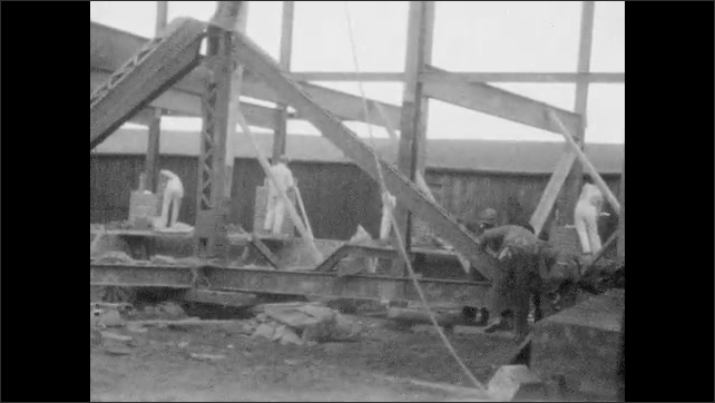 1920s: UNITED STATES: construction workers move frame into position. Workers on construction site. Men carry steel pillar.