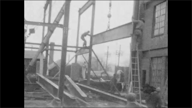 1920s: UNITED STATES: crane lifts metal beam onto building frame. Man moves beam into place.