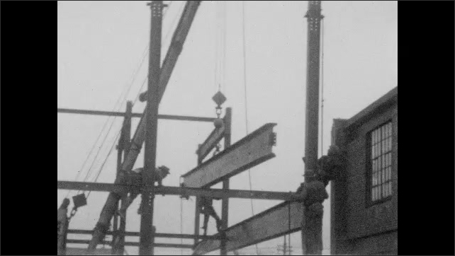 1920s: UNITED STATES: men build steel frame on construction site. Men guide beam into position. Crane lifts up beam.