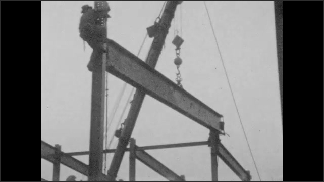 1920s: UNITED STATES: men climb up steel frame of construction. Horses wait with cart