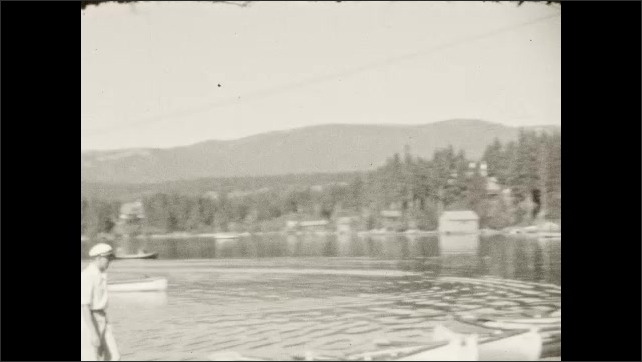 1930s: People stand on dock by lake. Boats drive on lake. People walk on dock. Woman and girl walk down dock, people sit on boat.
