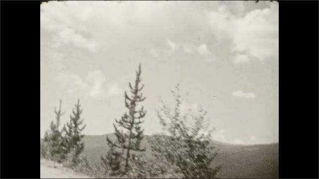 1930s: Dirt road leads up mountain. Trees, valley.