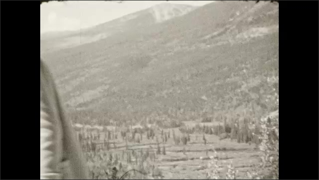 1930s: Woman and girl stand in front of mountains, look down at valley, walk away. Mountain range. Sign for Buttonhook Curve.