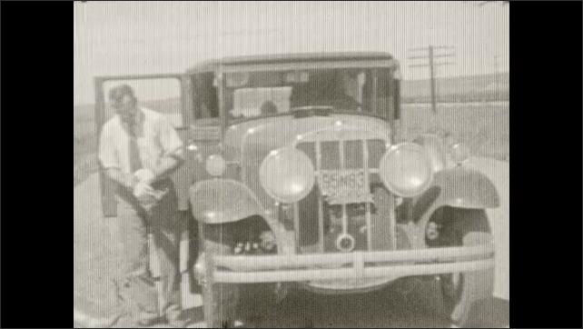 1930s: Car drives on mountain road. Trees, mountain range. Man gets out of car, puts on glove, turns crank on bottom of car.