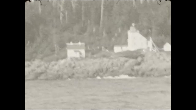 1930s: Buildings on rocky shore off water. Buildings on forested shore off water.