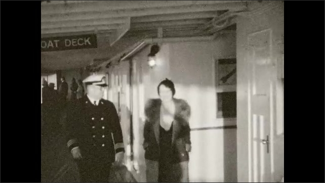 1930s: Woman in fur coat and ship captain walk on boat. Woman tosses horseshoes.