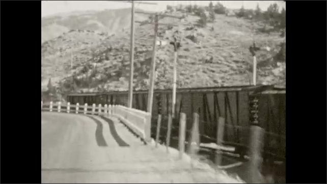 1930s: Driving down gravel road alongside mountain, mountain on horizon, train parallel to road. Driving alongside train. Man and woman drink from well on side of the road.