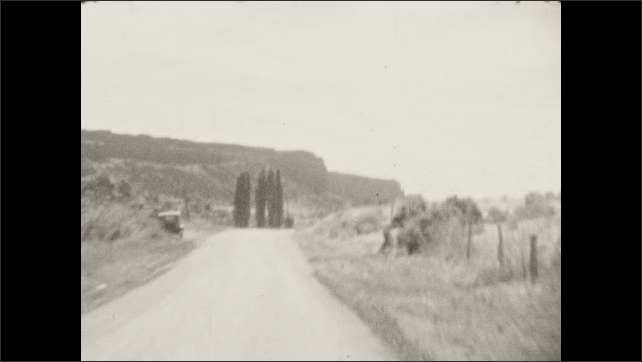 1930s: Driving down country road, fence and trees on either side, farmer walking on side of road. Driving down road on side of hill. Driving down country road, mountain on horizon. Crossing bridge.